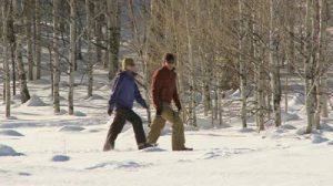 stock-footage-couple-walking-through-the-snow-with-snow-shoes-on